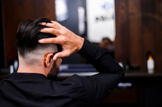 Vista posterior del hombre arreglando su cabello Foto gratis
