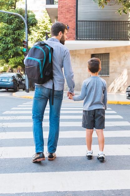Vista posterior de un hombre llevando una mochila escolar caminando en el paso de peatones con su hijo Foto gratis