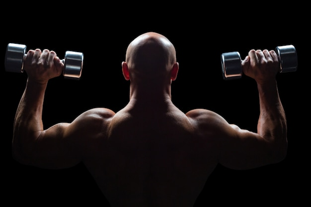 Vista posterior de hombre musculoso levantando pesas Foto Premium