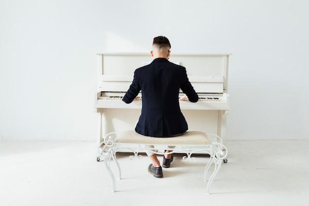 Vista posterior de un hombre tocando el piano sentado contra una pared blanca Foto gratis