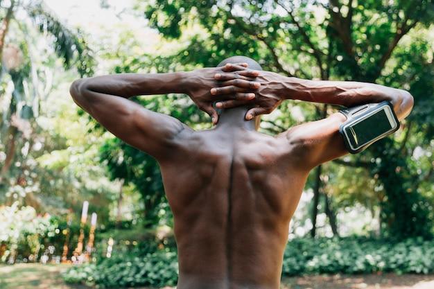 Vista posterior de un joven sin camisa con las manos detrás de la cabeza estirándose en el parque Foto gratis