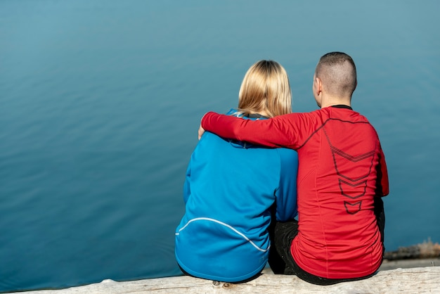 Vista posterior joven pareja abrazándose en el borde del lago Foto gratis