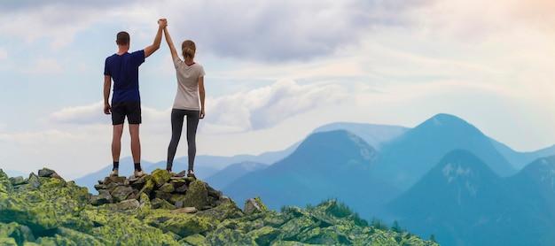 Vista posterior de la joven pareja de turistas, el hombre atlético y la chica delgada de pie con los brazos levantados tomados de la mano en la montaña rocosa. Foto Premium