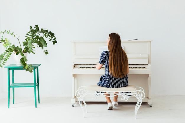 Vista posterior de una joven tocando el piano contra una pared blanca Foto gratis