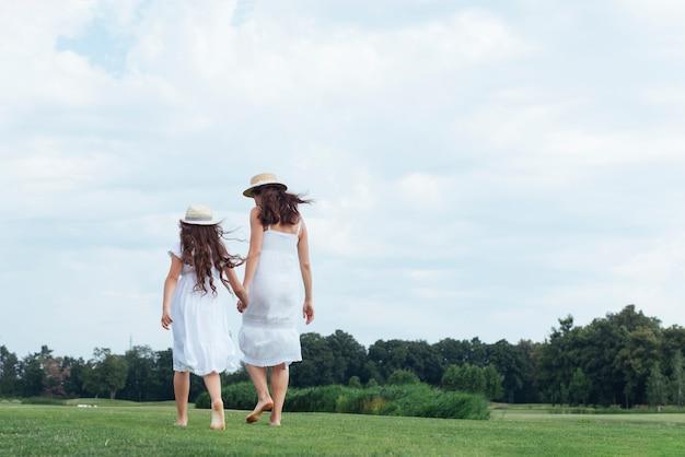 Vista posterior madre e hija caminando al aire libre Foto gratis
