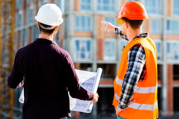 Vista posterior a medio tiro del ingeniero y arquitecto que supervisa la construcción. Foto gratis