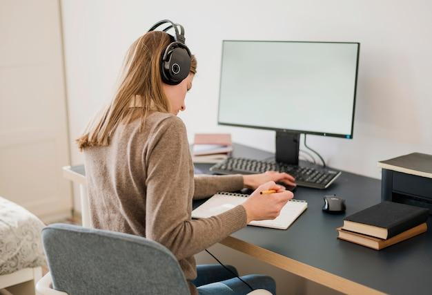 Vista posterior de la mujer con auriculares en el escritorio con una clase en línea Foto gratis