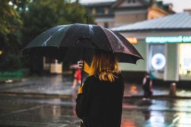 Vista posterior de la mujer caminando durante la lluvia en la ciudad Foto Premium