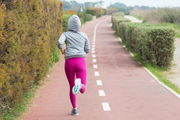 Vista posterior de la mujer deportiva en las polainas rosadas que se ejecutan sobre la pista Foto gratis