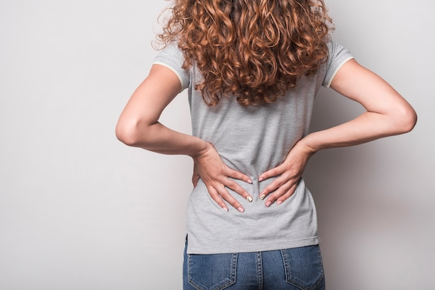 Vista posterior de la mujer con dolor de espalda contra el fondo gris Foto gratis