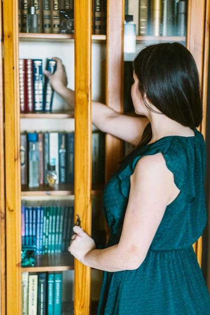 Vista posterior mujer elegir libro de estante Foto Gratis