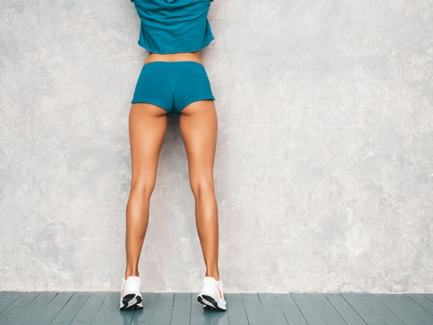 Vista posterior de la mujer de fitness confía en ropa deportiva buscando confianza. joven mujer vistiendo ropa deportiva. hermosa modelo con cuerpo bronceado perfecto. mujer posando en estudio cerca de la pared gris Foto gratis