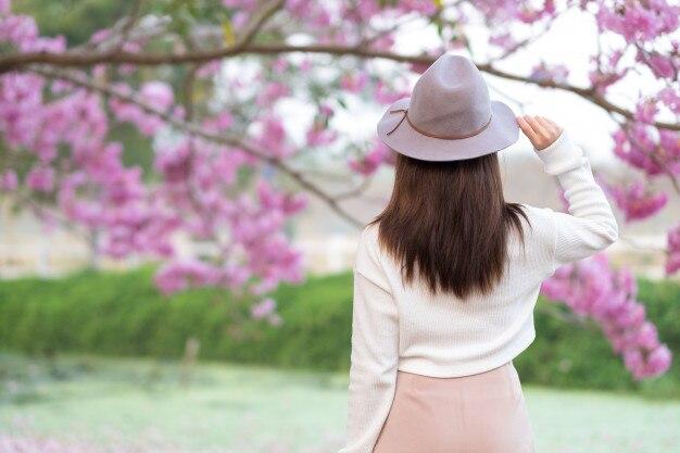 c8a38e880 Vista posterior de la mujer joven con el jardín de la flor de cerezo en día  de primavera | Descargar Fotos premium