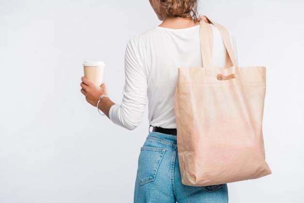 Vista posterior de la mujer joven en ropa casual con un vaso de café en la mano y un bolso de mano sobre el hombro Foto Premium