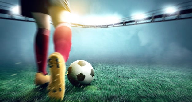 Vista posterior de la mujer del jugador de fútbol pateando la pelota en el campo de fútbol Foto Premium
