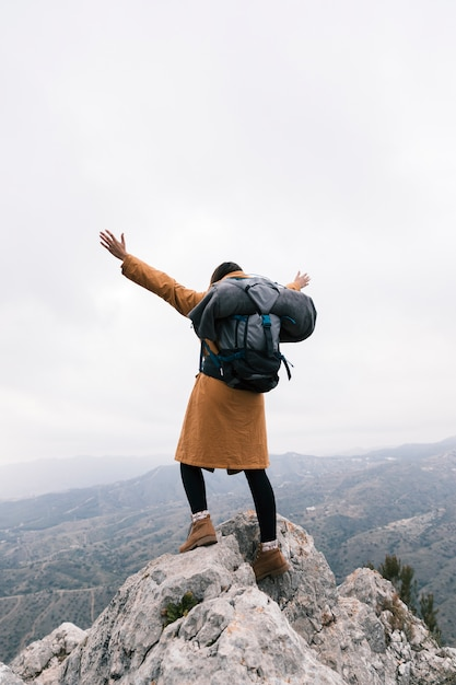 Vista posterior de una mujer levantando sus brazos de pie en la cima de la montaña Foto gratis