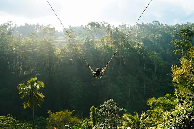 Vista posterior de la mujer mientras columpio con fondo de bosque natural en la luz del sol Foto Premium