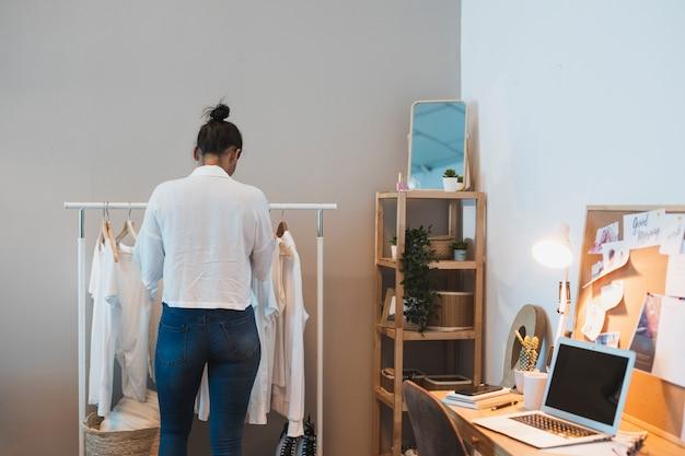 Vista posterior mujer mirando en el armario Foto gratis