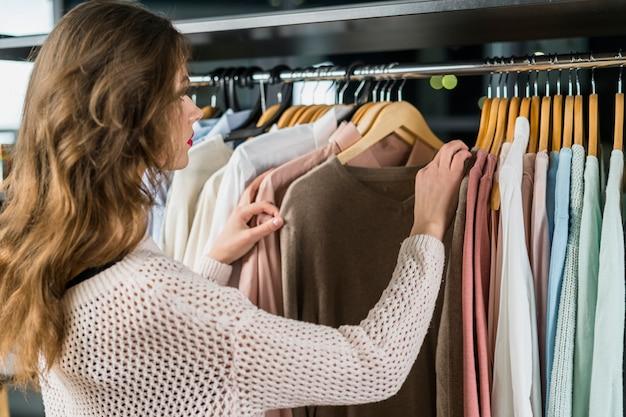 Vista posterior de una mujer mirando ropa en rack en sala de exposición Foto gratis