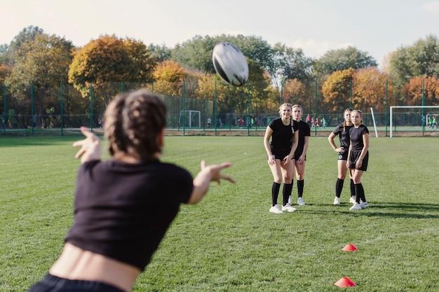 Vista posterior mujer pasando un balón de fútbol Foto gratis