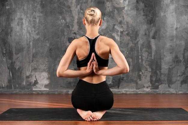 Vista posterior mujer posición compleja Foto gratis
