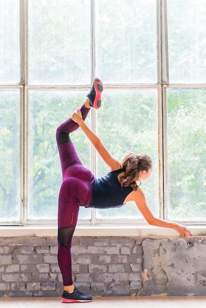 Vista posterior de una mujer que estira su pierna de pie sobre una pierna delante de la ventana Foto gratis