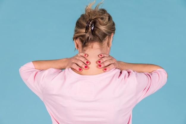 Vista posterior de la mujer que sufre de dolor de cuello contra fondo de pantalla azul Foto gratis