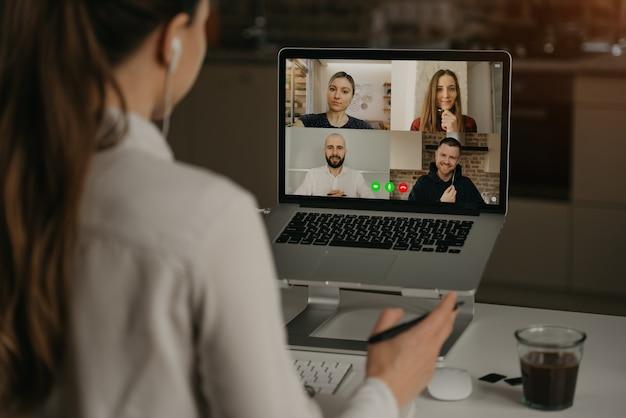 Vista posterior de una mujer que trabaja remotamente en una videoconferencia con sus colegas durante una reunión en línea. socios en una videollamada. equipo de negocios multiétnico discutiendo en una reunión en línea Foto Premium