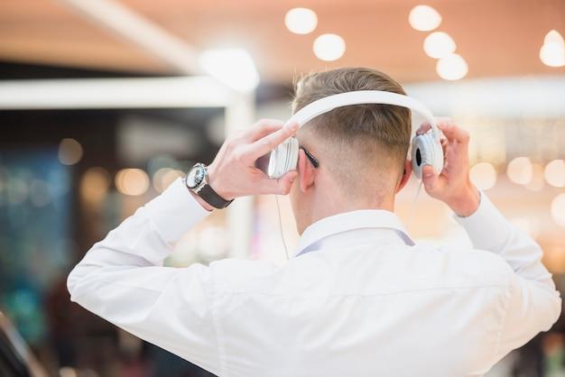 Vista posterior de una música que escucha del hombre joven en el auricular blanco Foto gratis