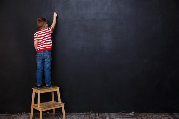 Vista posterior del niño lindo niño escribiendo con tiza Foto gratis