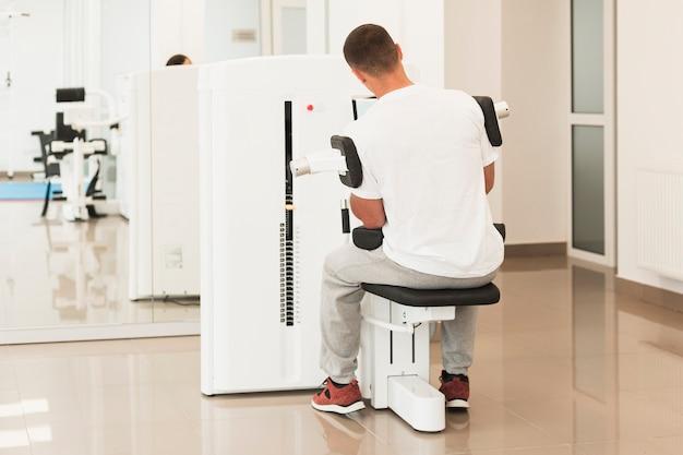 Vista posterior del paciente masculino haciendo ejercicios médicos Foto gratis