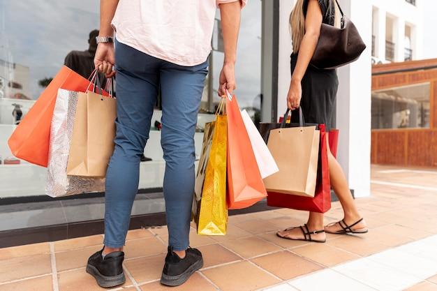 Vista posterior de la pareja con bolsas de compras Foto gratis
