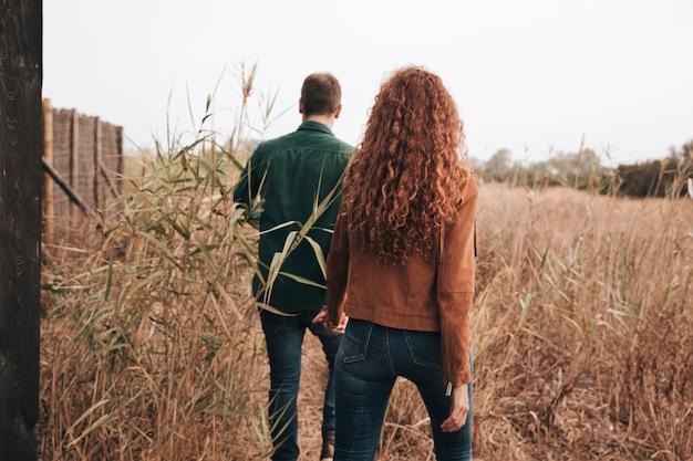 Vista posterior pareja caminando por el campo de trigo Foto gratis