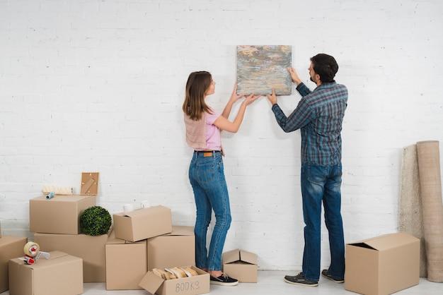 Vista posterior de una pareja joven colocando un marco de fotos en una pared blanca con cajas de cartón Foto gratis