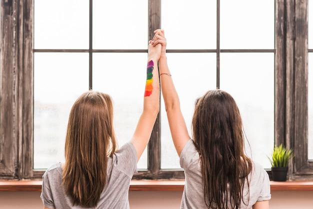 Vista posterior de la pareja de lesbianas jóvenes tomándose las manos de cada uno de pie frente a la ventana Foto gratis
