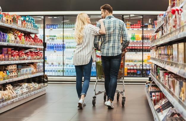 Vista posterior de una pareja sonriente caminando con un carrito Foto gratis