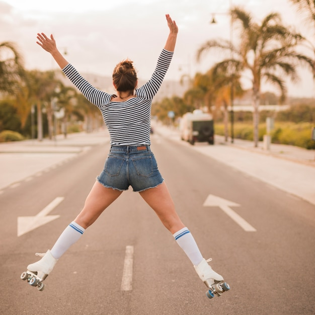 Vista posterior de una patinadora con las piernas separadas y los brazos levantados saltando en el camino Foto gratis