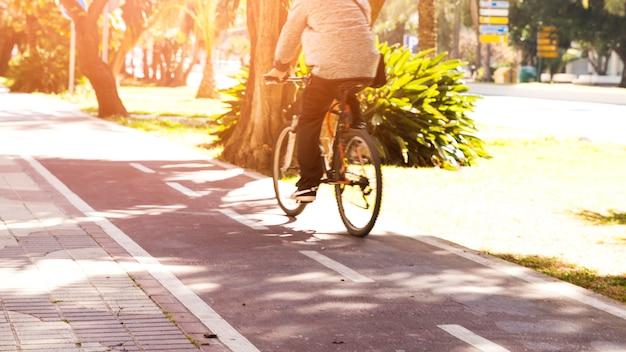 Vista posterior de una persona que monta la bicicleta en el carril bici Foto gratis