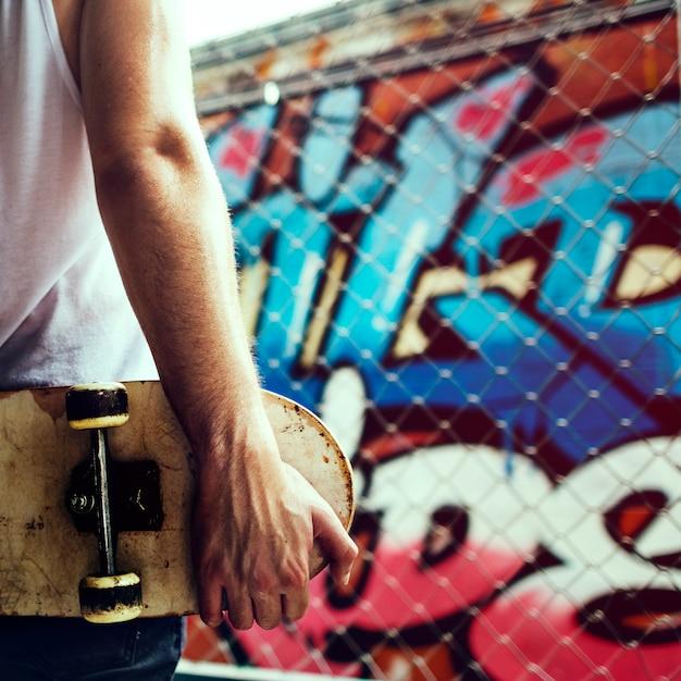 Vista posterior del primer del brazo que sostiene el monopatín con el fondo de la pared del graffiti Foto gratis