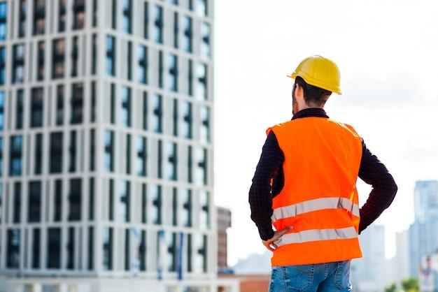 Vista posterior de tiro medio del arquitecto que supervisa la construcción Foto gratis