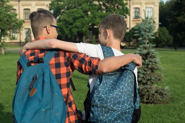 Vista posterior tiro medio de dos adolescentes abrazándose Foto gratis