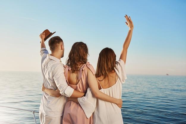 Vista posterior de tres mejores amigos que viajan en bote abrazando y saludando mientras mira al mar. las personas que están de vacaciones de lujo se saludan para enviar una pista que pasa en yate. Foto gratis