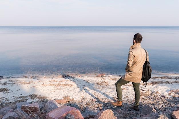 Vista posterior de un viajero masculino mirando el paisaje marino tranquilo Foto gratis