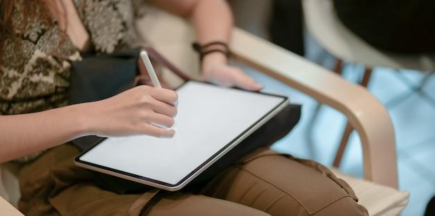 Vista de primer plano de un joven diseñador profesional que trabaja en su proyecto mientras dibuja en una tableta Foto Premium