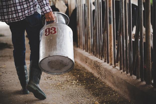Vista de primer plano de las piernas de un granjero trabajando con heno en el establo de animales Foto gratis