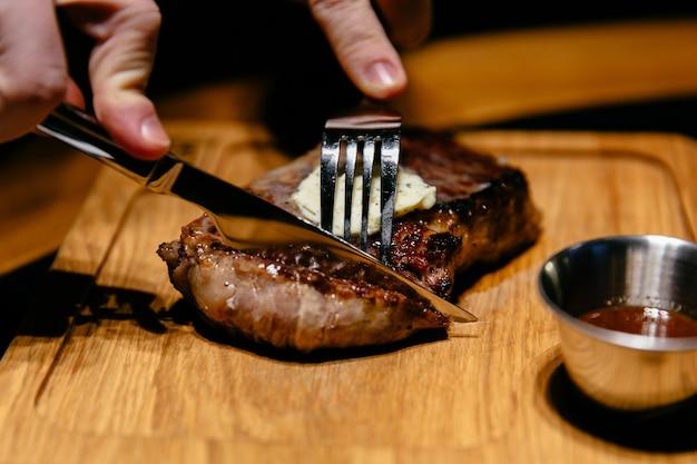 Vista de primer plano de sabroso bistec con salsa. las manos masculinas comienzan a cortar una rebanada. Foto gratis