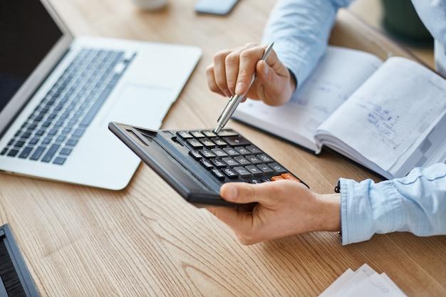 Vista recortada del gerente profesional de finanzas serias, sosteniendo la calculadora en las manos, verificando las ganancias del mes de la compañía Foto gratis