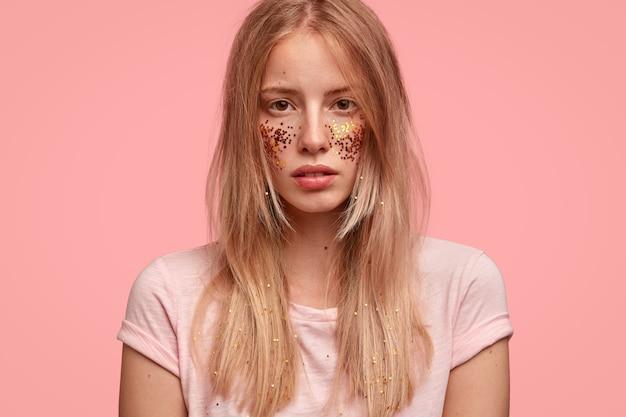Vista recortada de una mujer hermosa que ha decorado las mejillas con destellos, se ve con confianza Foto gratis