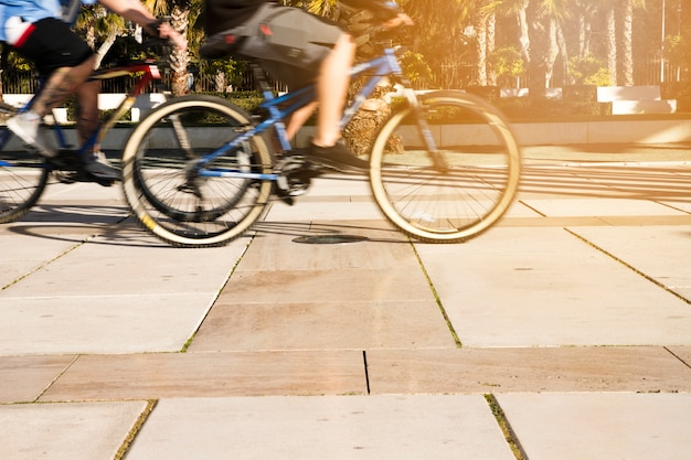 Vista de sección baja de personas montando bicicleta en la ciudad Foto gratis