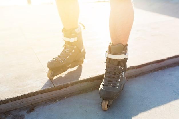Vista de sección baja de los pies de un hombre con patines en línea Foto gratis